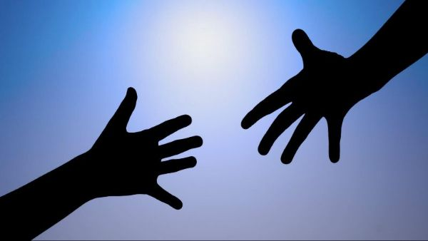 A silhouette of two hands reaching toward each other.