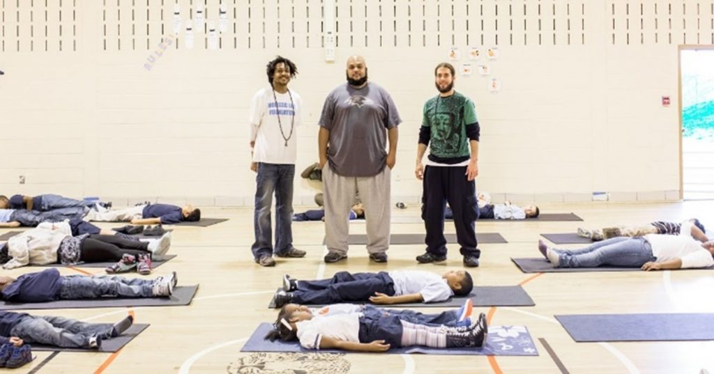Students resting on yoga mats, with Holistic Life Foundation founders nearby.