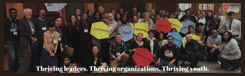 """Photo of YDEKC leaders at a Member Summit, with the tagline, """"Thriving Leaders. Thriving Organizations. Thriving Youth."""""""